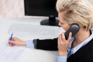 geschäftsfrau am telefon notiert etwas in unterlagen